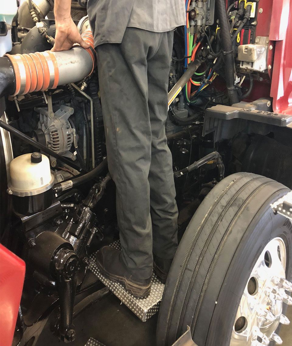 Drag Link Stand ladder on truck with mechanic servicing hard-to-reach parts of engine